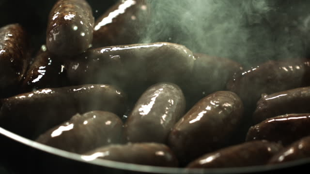 Slow motion shot of sausages being tossed in a frying pan.