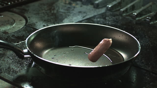 slow motion shot of sausages falling into a frying pan. - sausage stock videos & royalty-free footage