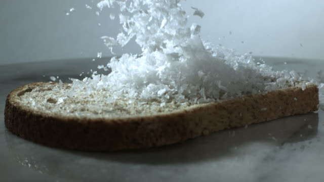 Slow motion shot of sea salt falling onto a piece of brown bread.