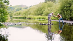 Slow Motion Shot Of Senior Couple Using Stepping Stones To Cross River Whilst Hiking In UK Lake District
