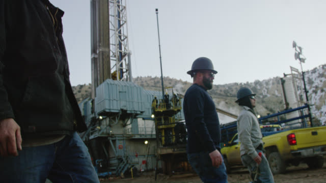 slow motion shot of several male oilfield workers walking through an oil and gas drilling pad site on a cold, winter morning - manual worker stock videos & royalty-free footage