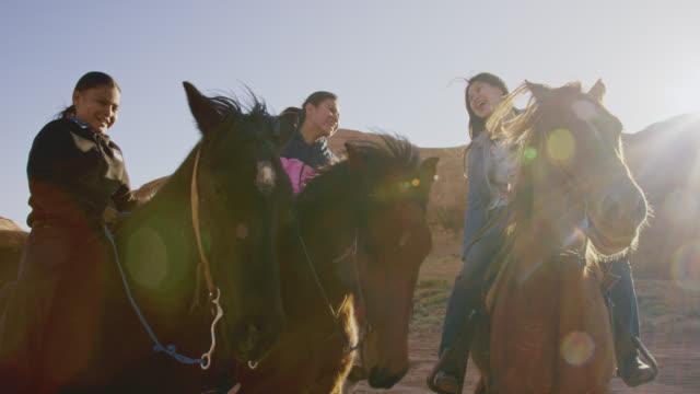 scatto al rallentatore di diversi bambini nativi americani (navajo) che ridono e sorridono mentre siedono sui loro cavalli all'aperto in una giornata luminosa - tribù del nord america video stock e b–roll