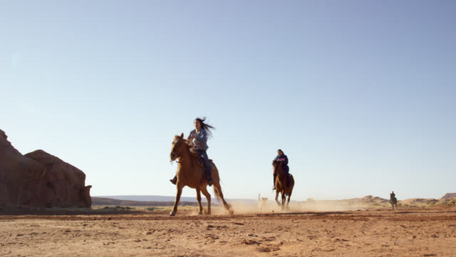 vídeos de stock e filmes b-roll de slow motion shot of several teenaged native american girls (navajo) riding horses through the monument valley desert with their pet dogs in arizona/utah next to a large rock formation on a clear, bright day - cultura tribal da américa do norte