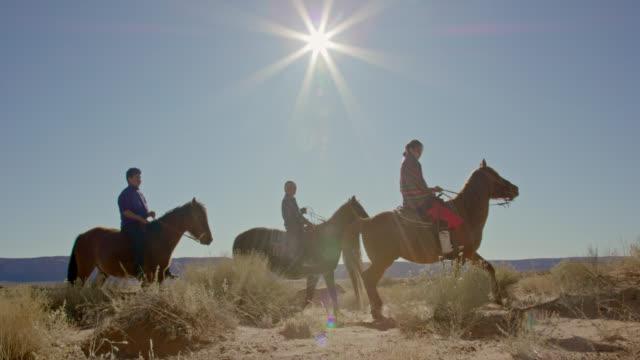 slow motion shot von mehreren jungen indianerkindern (navajo) kinder, die an einem klaren, hellen tag mit ihren haustierhunden in arizona/utah durch die monument valley desert reiten - nordamerikanisches indianervolk stock-videos und b-roll-filmmaterial