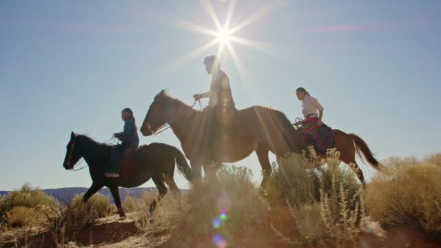 slow motion shot of several young native american (navajo) children riding horses through the monument valley desert with their pet dogs in arizona/utah on a clear, bright day - north american tribal culture stock videos & royalty-free footage