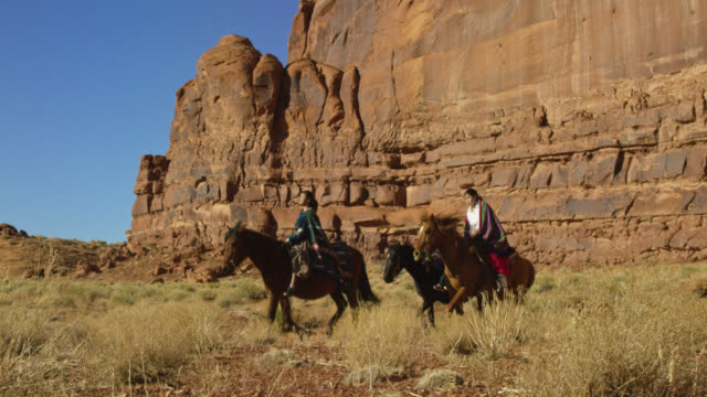 slow motion shot of several young native american (navajo) children riding horses through the monument valley desert in arizona/utah next to a large rock formation on a clear, bright day - navajo culture stock videos & royalty-free footage