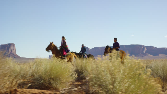 slow motion shot of several young native american (navajo) children riding horses through the monument valley desert with their pet dogs with large rock formations in the distance in arizona/utah on a clear, bright day - horse family stock videos & royalty-free footage