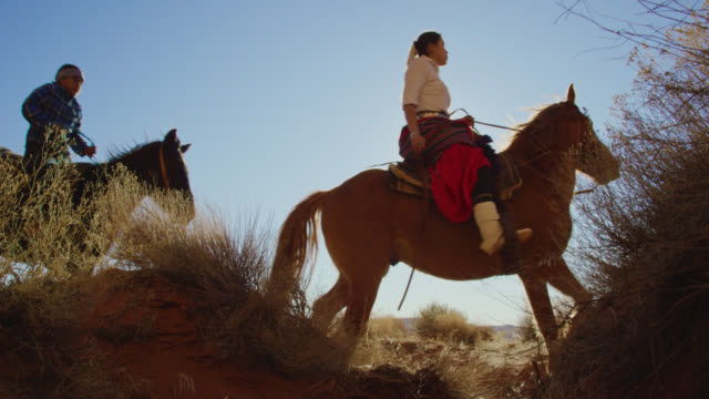 slow motion shot of several young native american (navajo) people riding horses through a ravine in the monument valley desert in arizona/utah on a clear, bright day - small group of animals stock videos & royalty-free footage