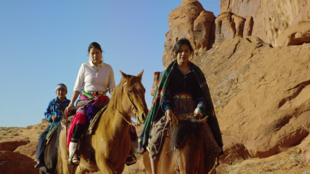 stockvideo's en b-roll-footage met slow motion shot of several young native american (navajo) people riding horses through the monument valley desert in arizona/utah next to a large rock formation on a clear, bright day - recreatief paardrijden