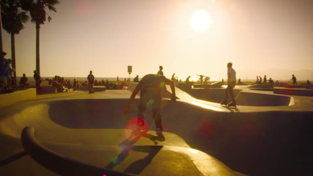 slow motion shot of skateboarder and rollerblader in skate park near venice beach, california - eislaufen stock-videos und b-roll-filmmaterial