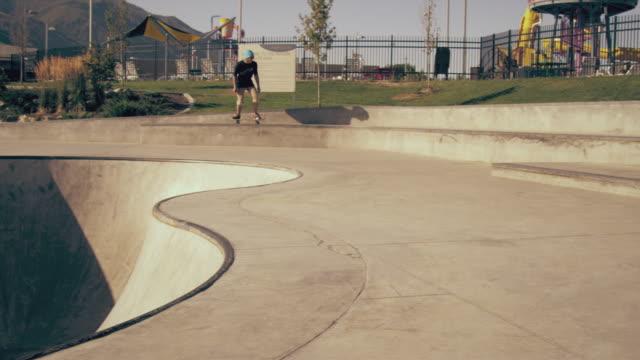 Slow motion shot of skateboarder falling after trying to kickflip a gap at a skatepark.