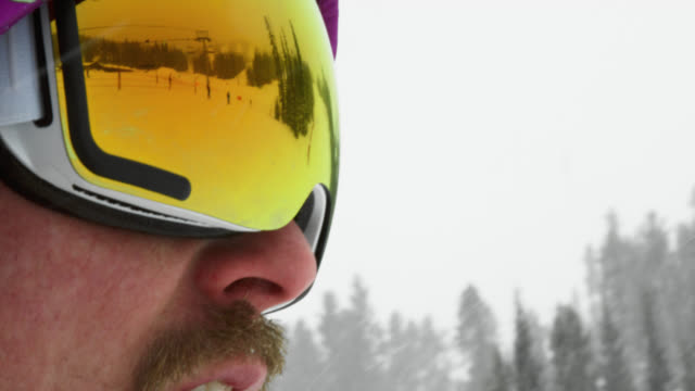 slow motion shot of skiers skiing down a ski run in the reflection of a male snowboarder's goggles on an overcast winter day on the ski slopes - ski goggles stock videos & royalty-free footage