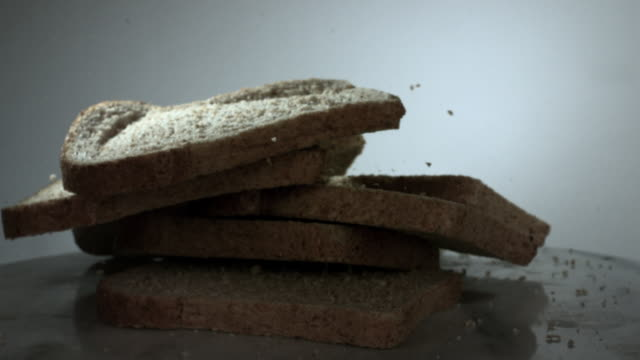 slow motion shot of slices of brown bread falling onto a table. - brown bread stock videos and b-roll footage