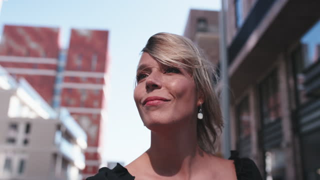 slow motion shot of smiling blond woman in city - standing stock videos & royalty-free footage