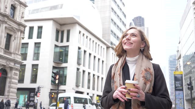 slow motion shot of smiling blond woman with coffee to go in london - 金髪点の映像素材/bロール