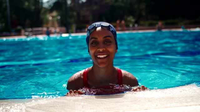 slow motion shot of smiling female swimmer at pool edge - swimming goggles stock videos & royalty-free footage