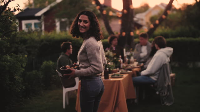 Slow motion shot of smiling female with bowl walking towards dining table in backyard
