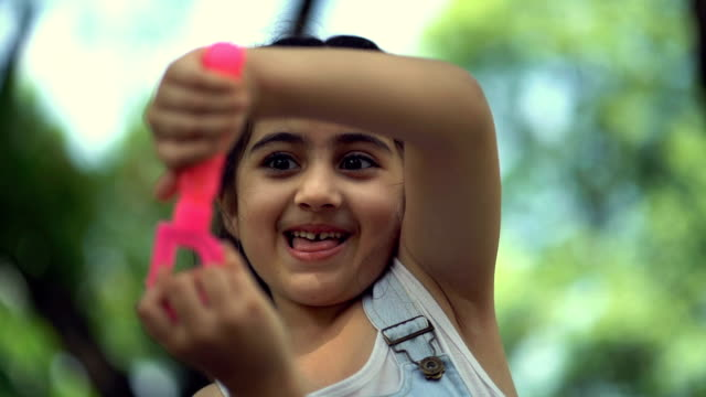 slow motion shot of smiling girl blowing soap bubbles in summer park - islam stock videos & royalty-free footage