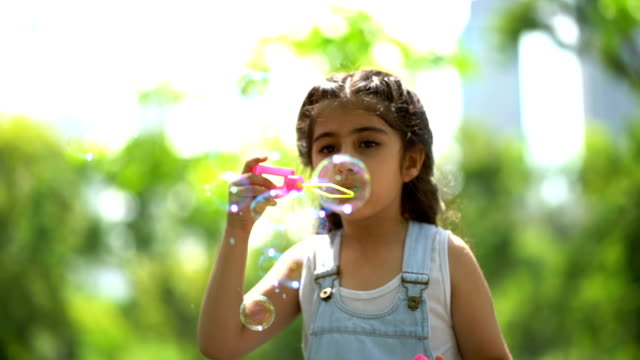 slow motion shot of smiling girl playing with soap bubbles - middle eastern ethnicity stock videos & royalty-free footage