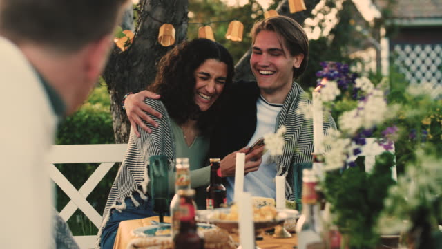 Slow motion shot of smiling heterosexual couple using smart phone while sitting at garden party