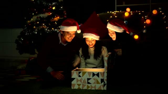 vídeos de stock, filmes e b-roll de tiro do movimento lento do miúdo de sorriso que abre uma caixa de presente com raios de luz de explosão de brilho no tempo do natal - mágico