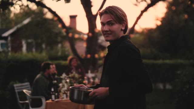 Slow motion shot of smiling male with bowl walking towards dining table in backyard