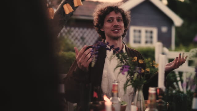 Slow motion shot of smiling man talking to friends while sitting in yard during garden party