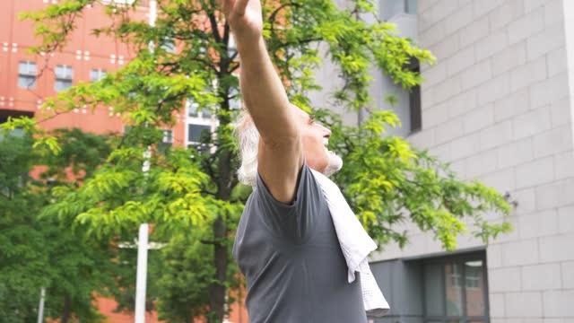 vidéos et rushes de slow motion shot of smiling senior athletic man with arms raised - bras humain