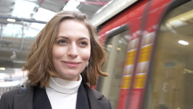 slow motion shot of smiling woman at station - joy stock-videos und b-roll-filmmaterial