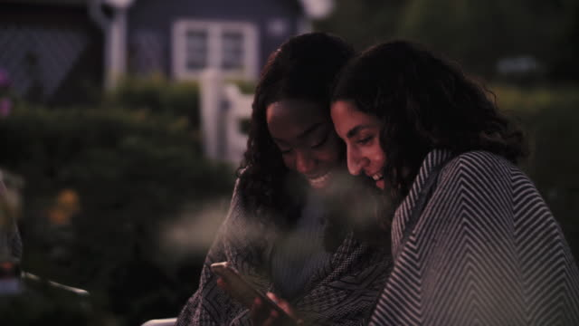 Slow motion shot of smiling women using phone while sitting in yard during dinner party