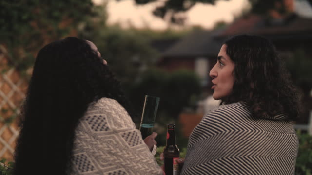 slow motion shot of smiling women with drinks talking while standing in yard during dinner party - blanket stock videos & royalty-free footage