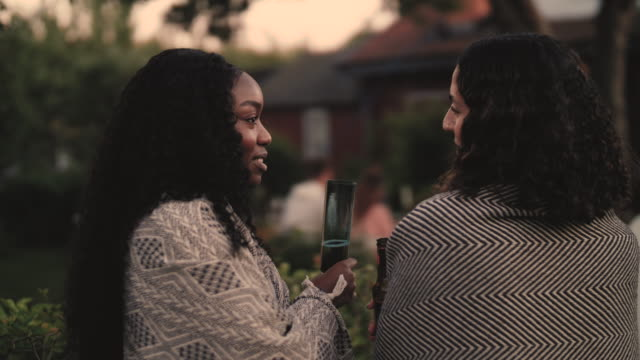 Slow motion shot of smiling women with drinks talking while standing by yard during dinner party