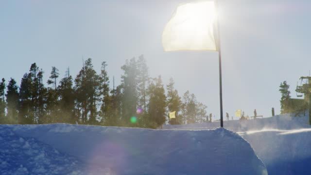 明るく晴れた晴れた日にコロラド州のスキーリフトを背景に走るスキージャンプで旗を吹く空中と風に渦巻く雪のスローモーションショット - ゲレンデ点の映像素材/bロール