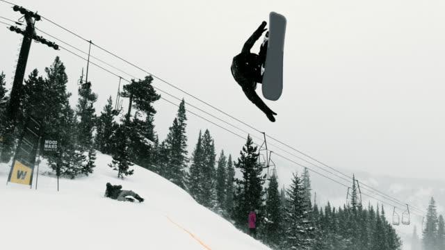 "slow motion shot of snowboarder in full winter gear completing a ""switch 540 tail grab"" trick on a jump with a forest and a ski jump in the background at eldora ski resort near boulder, colorado on a snowy, overcast day - ski resort stock videos & royalty-free footage"