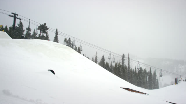 フルウィンターギアのスノーボーダーのスローモーションショットは、遠くから雪の日、曇りの日にコロラド州ボルダー近くのエルドラスキーリゾートで、森とスキーリフトを背景にジャン� - ゲレンデ点の映像素材/bロール