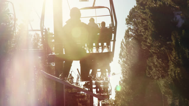 slow motion shot of snowboarders riding a ski lift at eldora ski resort near boulder, colorado on a bright, clear day - ski lift stock videos & royalty-free footage