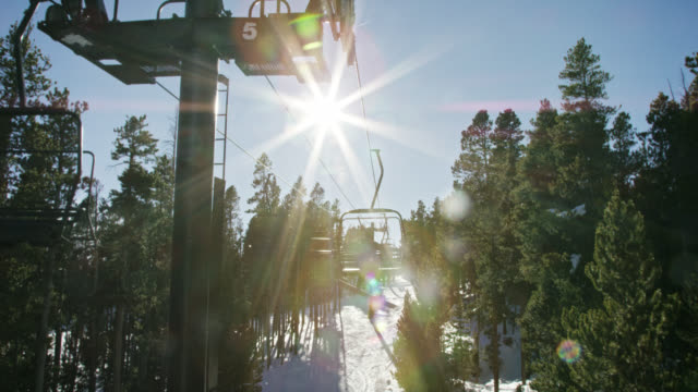 slow motion shot of snowboarders riding a ski lift at eldora ski resort near boulder, colorado on a bright, clear, sunny day - ski holiday stock videos & royalty-free footage
