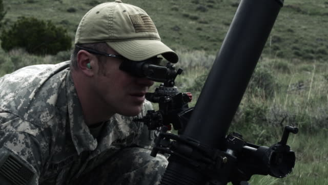 Slow motion shot of soldier aiming mortar launcher.