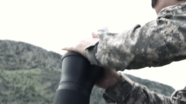 Slow motion shot of soldiers firing mortar and checking target area.
