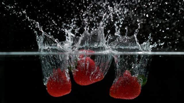 stockvideo's en b-roll-footage met slow motion shot van aardbeien spatten in het water - aardbei