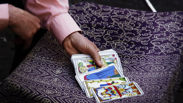 slow motion shot of tarot card reading fanning cards on table - tarot cards stock videos & royalty-free footage