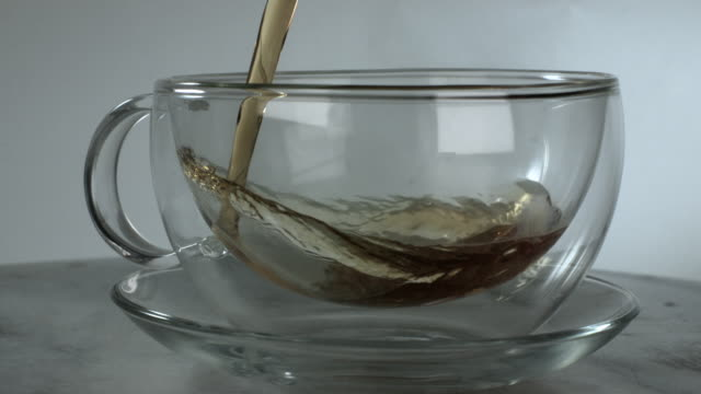 slow motion shot of tea being poured into a glass cup. - heißes getränk stock-videos und b-roll-filmmaterial