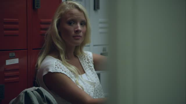 slow motion shot of teenage girl sitting by locker missing part of left arm. - locker stock videos & royalty-free footage