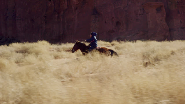 vídeos de stock e filmes b-roll de slow motion shot of ten-year-old native american boy (navajo) galloping on his horse to catch up to a teenaged girl in the monument valley desert in arizona with her pet dogs next to a large rock formation on a sunny day - cultura tribal da américa do norte