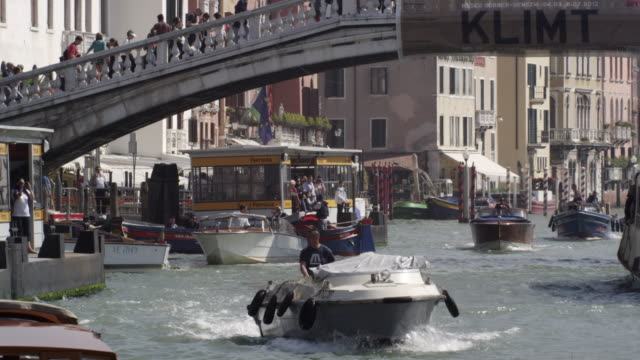 slow motion shot of the busy grand canal with tourists crossing the ponte scalzi bridge - ponte stock-videos und b-roll-filmmaterial