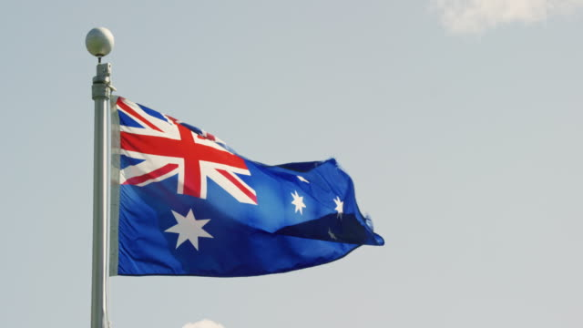 slow motion shot of the flag of australia blowing in the wind on a sunny day - identity politics stock videos & royalty-free footage