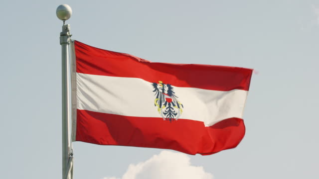 slow motion shot of the flag of austria blowing in the wind on a sunny day - austria video stock e b–roll