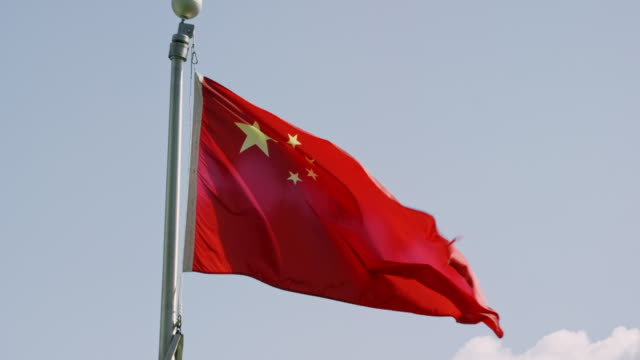 slow motion shot of the flag of china blowing in the wind on a sunny day - chinese flag stock videos & royalty-free footage