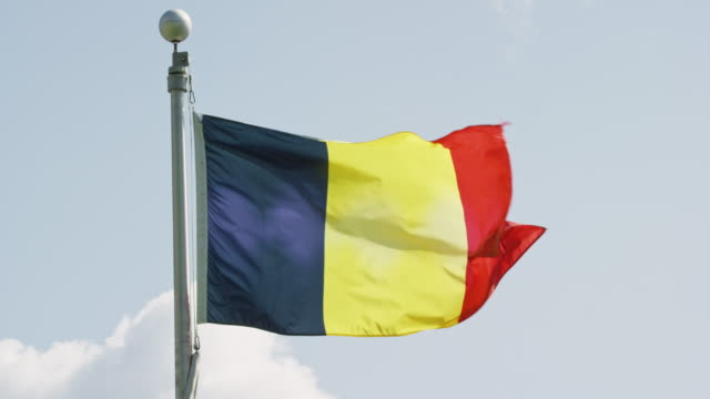 slow motion shot of the flag of romania blowing in the wind on a sunny day - romania stock videos & royalty-free footage