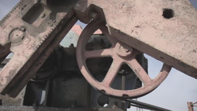 vídeos de stock, filmes e b-roll de slow motion shot of the mechanism of a pumpjack turning. - poço de petróleo